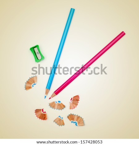 picture of some colored pencils and a pencil sharpener on a beige background, with a retro effect