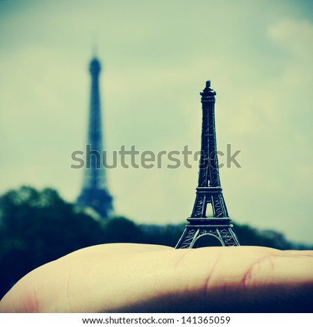 picture of someone holding a reproduction of the Eiffel Tower with the real Eiffel Tower in the background, in Paris, France, with a retro effect