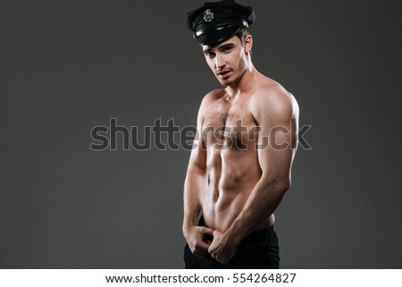 Picture of stripper policeman standing over grey background wearing police hat.