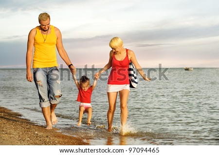Picture of strolling young family on sea beach