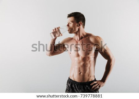 Picture of strong serious young sportsman standing isolated over grey background and drinking water. Looking aside. #739778881