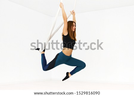 Picture of stylish young European female gymnast stretching leg while hanging in hammock in white room, performing aerial antigravity fly yoga exercise in flexibility, balancr and stength, backbending