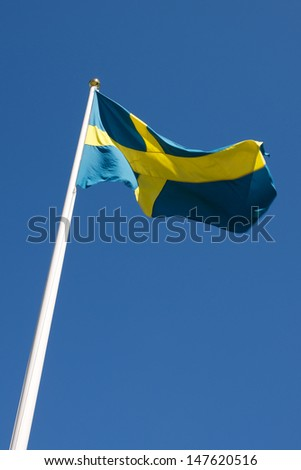 Picture of Swedish flag waving in the wind, on a blue sky