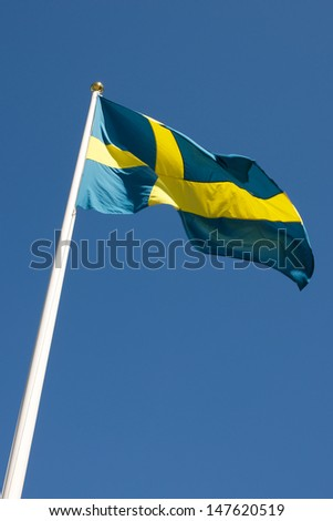 Picture of Swedish flag waving in the wind, on a blue sky  Picture of Swedish flag waving in the wind, on a blue sky
