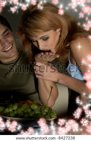 picture of sweet couple eating grapes surrounded by flowers