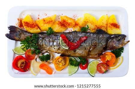 Picture of  tasty baked whole  trout  with potatoes, greens and tomatoes on white plate. Isolated over white background