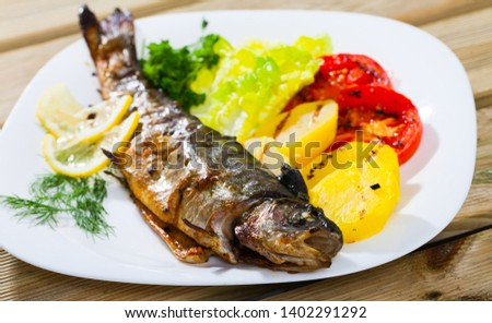 Picture of  tasty baked whole  trout  with potatoes, greens and tomatoes on white plate
