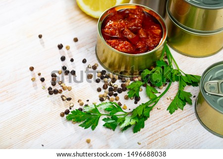 Picture of  tasty squids in American Salsa on background with greens and lemon