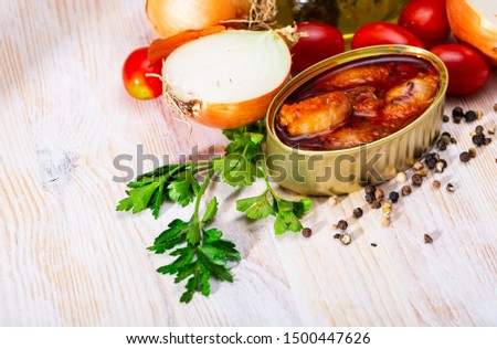 Picture of  tasty stuffed squid in tomato sauce on background with greens, tomatoes and onion