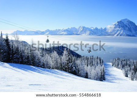 Picture of temperature inversion at Lake Louise, causing a cloud of sea with gondola visible. #554866618