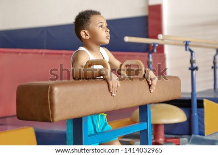 Picture of ten year old Afro American kid in white t-shirt standing by pommel horse at gym, having thoughtful facial expression, dreaming that he wins artistic gymnastics world champinonship