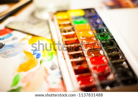 Picture of the artist illustrator workbench table with watercolors, brushes, paper, palette  #1137831488