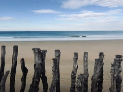 Picture of the Horizon in Saint Malo, France. Wooden breakwaters on the foreground to break powerful incoming waves.