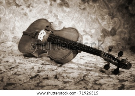 Picture of the old italian violin on a fabric drapes