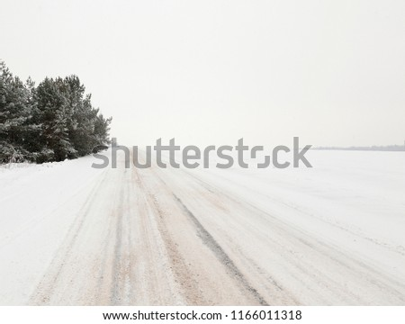 picture of the road in the winter season. Close-up, on the snow-covered asphalt stripes visible from the tires of the car