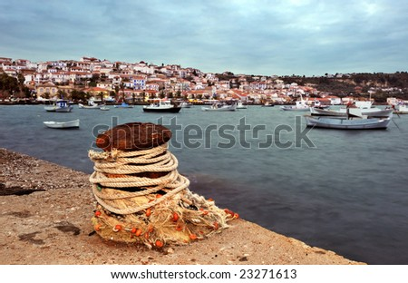 Picture of the seaside town of Koroni, in southern Peloponnese, Greece, showing a bollard in the foreground. Boats show some motion blur from long exposure