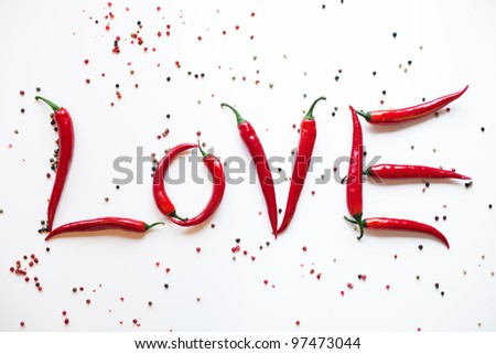 picture of the word love written with red chili peppers arranged with different colored peppercorns