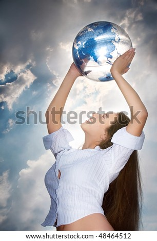 Picture of the young beautiful girl with blue globe against the sky