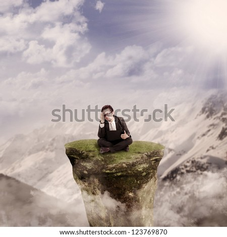 Picture of thinking businessman sitting with his laptop on a mountain rock