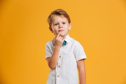Picture of thinking little boy child standing isolated over yellow background. Looking aside.