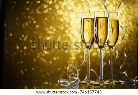Picture of three glasses with champagne on gold background. #746157745