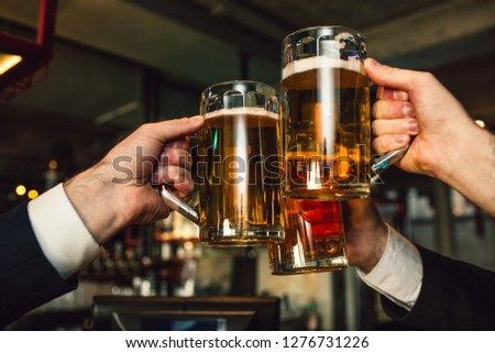 Picture of three mugs of beer in men hands. People wear suits. They are in bar.