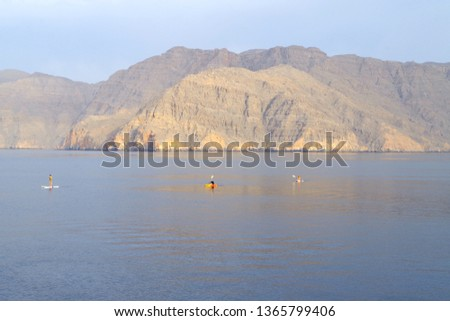 Picture of tourists with paddles and kayak and enjoying a morning activity in a spectacular environment with cristal waters between cliffs. Pure tourists paradise.