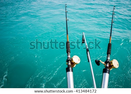 Picture of two commercial fishing poles over turquoise water with copy space