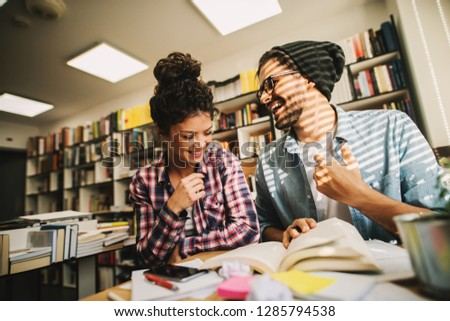 Picture of two cute young urban students sitting in bright library and learning together. Smiling and helping each other.