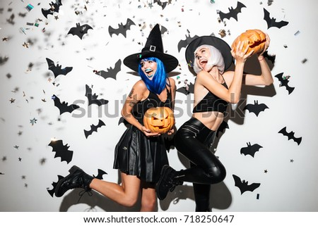Picture of two emotional young women in halloween costumes on party over white background with pumpkin. Looking aside.