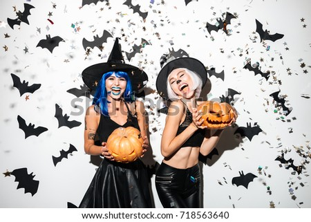 Picture of two emotional young women in halloween costumes on party over white background with pumpkin. Looking camera.