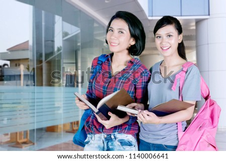Picture of two female college students smiling at the camera while holding a book