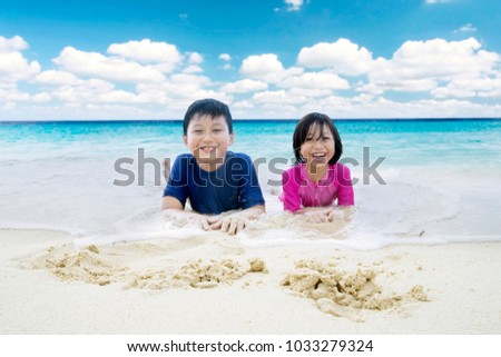 Picture of two little children looks happy while lying on the sand. Shot in the beach