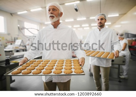 Picture of two male food factory employees in sterile clothes holding trays full with fresh cookies. Working on production line in food factory.