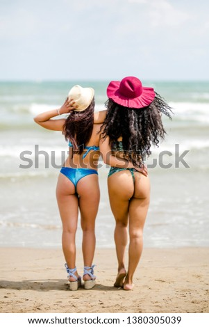 Picture of two sexy best girlfriends in bikini looking the sea