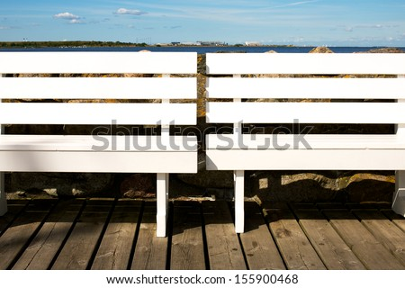 Picture of two white benches at a marina. Sea in the background