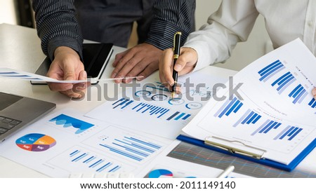 Picture of two young businessmen at a meeting Analyzing the financial markets, the youngster works in the office on his laptop while sitting at a wooden desk and analyzing the documents in hand. finan Imagine de stoc ©