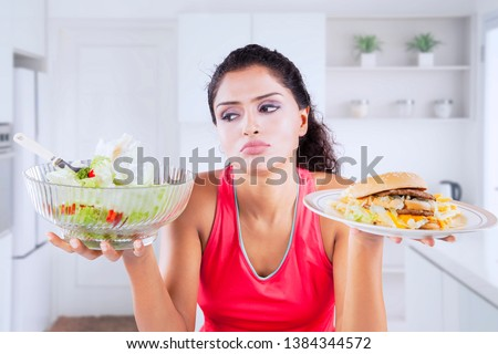 Picture of unhappy Indian woman looks confused while choosing a vegetable salad or hamburger in the kitchen #1384344572