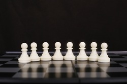 Picture of white chess pawns on the chessboard. isolated on the black background.