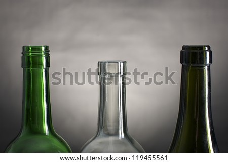 Picture of wine bottle necks on a row, on a grey and black background