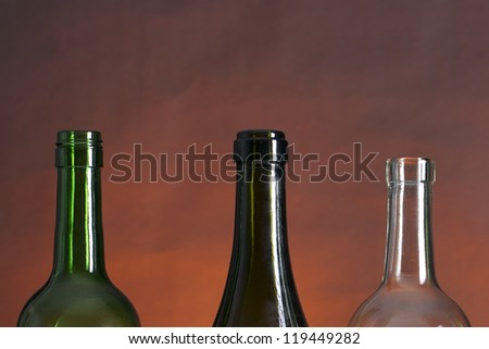Picture of wine bottle necks on a row, on a red and black background