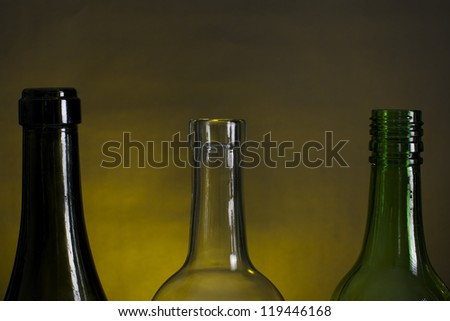 Picture of wine bottle necks on a row, on a yellow and black background