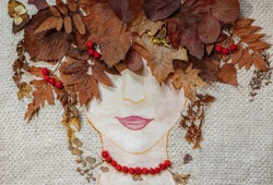 picture of woman's face with collage of dried leaves and berries over the head, crown of colorful leaves, woman - autumn, miss autumn