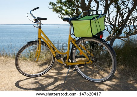 Picture of yellow bicycle with a picnic basket on