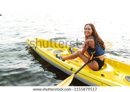 Picture of young beautiful happy woman kayaking on lake sea in boat looking camera.