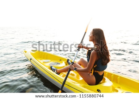 Picture of young beautiful woman kayaking on lake sea in boat.