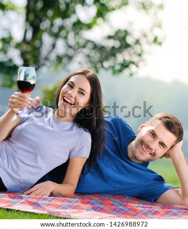 Picture of young couple in love, lying together on a picnic blanket with wine, outdoors