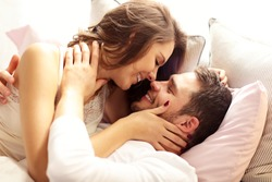 Picture of young couple kissing in bed