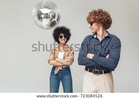 Picture of young emotional smiling retro loving couple standing isolated. Looking at each other near disco ball.