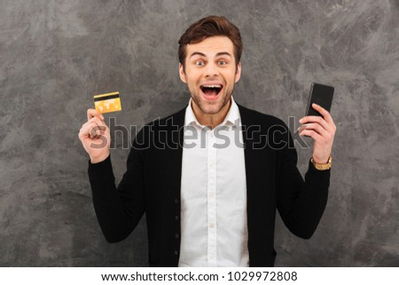 Picture of young excited businessman standing over grey wall background. Looking camera chatting by mobile phone holding credit card.